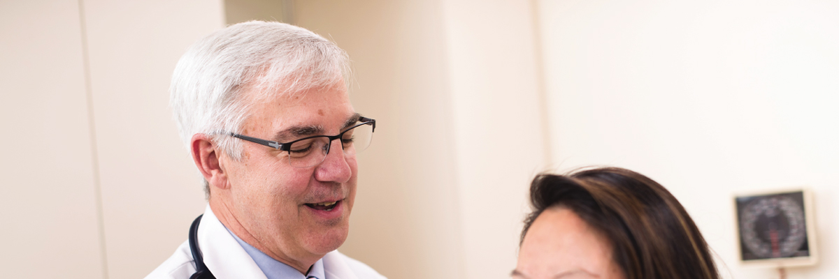 MSK Endocrinologist Michael Tuttle examines a woman for thyroid cancer.